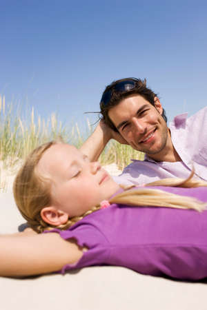 Germany Baltic sea Father and daughter 67 lying in beach dunes portrait