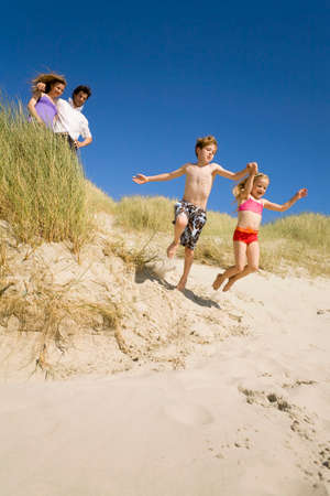 Germany Baltic sea Family in sand dunes children jumping down sand dunes
