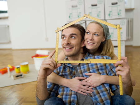 Young couple making house shape with folding rule portrait LANG_EVOIMAGES