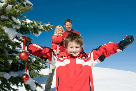 Italy South Tyrol Seiseralm Boy 45 holding Christmas baubles parents in background portrait LANG_EVOIMAGES