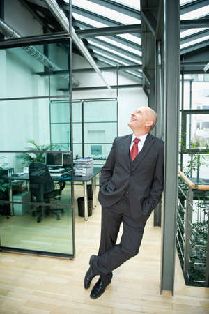 Germany Munich Businessman standing in office hands in pockets LANG_EVOIMAGES