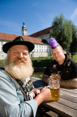 Germany Bavaria Upper Bavaria Man with mohawk hairstyle and Bavarian man in beer garden