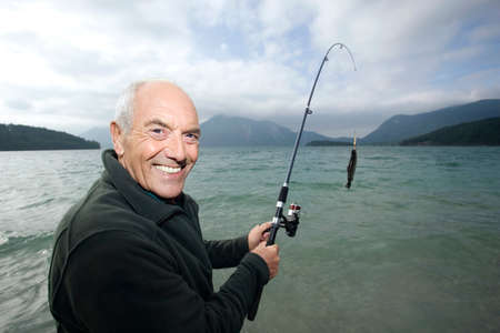 Germany Bavaria Walchensee Senior man fishing in lake