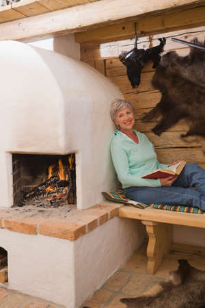 Senior woman in hunting lodge holding a book