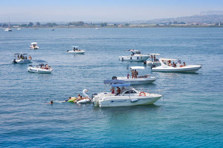 Syracuse, Sicily, Italy - august 12, 2018: people float on boats Editorial