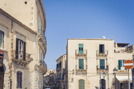 View of old street, facades of ancient buildings in seafront of Ortygia (Ortigia) Island, Syracuse, Sicily, Italy