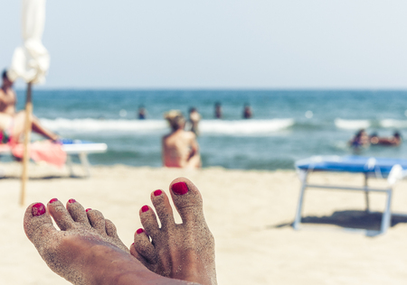 View of the beach of Catania, Sicily, Italy, soft focus, female legs in the foreground