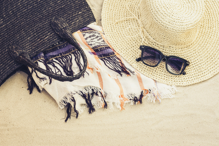 Vintage summer wicker straw beach bag, sun glasses, hat cover-up beachwear wrap on the sand, tropical background