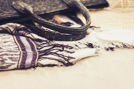 Vintage summer wicker straw beach bag, hat and cover-up beachwear wrap on the sand Foto de archivo