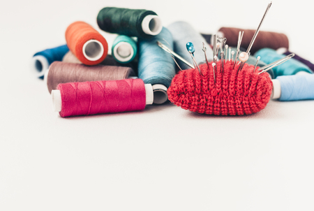 Red knitted needle pad for sewing and colored thread coils on white background with copy space for text
