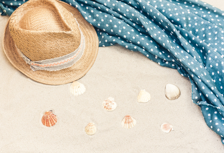Vintage summer wicker straw beach hat and cover-up beachwear wrap on the sand, tropical background