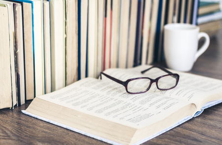 Stack of books education background, open book, glasses, and cup of tea with lemon 免版税图像