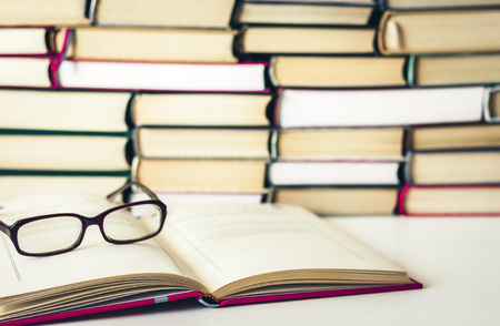 Books background, open book and glasses on white wooden table in office business background for education learning concept