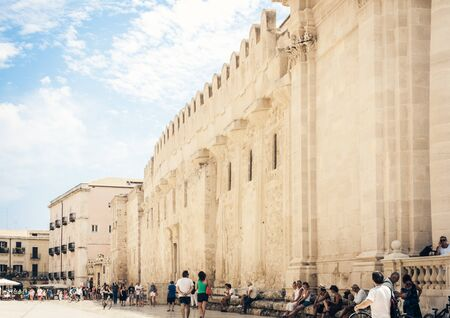 Syracuse (Siracusa), Sicily, Italy – august 12, 2018: Tourists walking on ancient square Piazza del Duomo with old buildings in Ortygia (Ortigia) Island