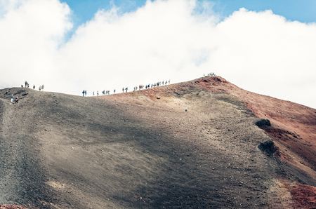 People walking on Mount Etna, active volcano on the east coast of Sicily, Italy