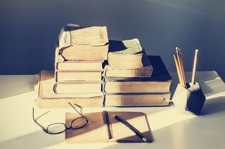 Stack of old books, textbook, notebook, glasses and pencils on white table in office background for education retro concept