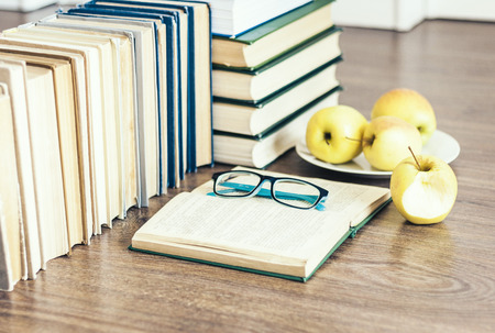 Stack of books, open book, glasses and green apples, background for education learning concept