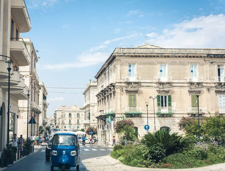 Syracuse (Siracusa), Sicily, Italy – august 12, 2018: Tourists walking on ancient street with old buildings in Ortygia (Ortigia) Island