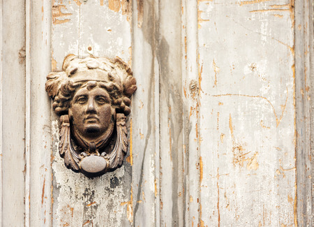 Exterior vintage door knocker metal circle on a wooden door of an ancient building in Catania, Sicily, Italy