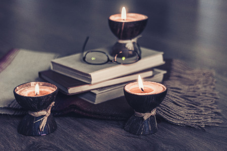 Burning spa aroma candles in coconut shell, plaid, glasses and books, cozy home interior background 스톡 콘텐츠