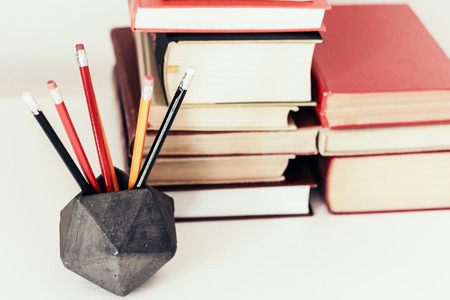 Stack of book education concept background, many books piles and pencils in concrete holder on white table with copy space for text Zdjęcie Seryjne - 122497150
