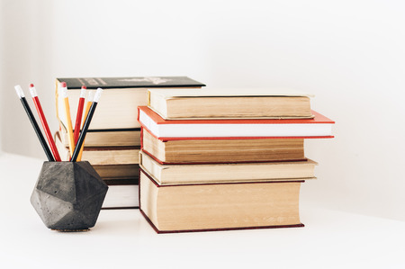 Stack of book education concept background, many books piles and pencils in concrete holder on white table with copy space for text