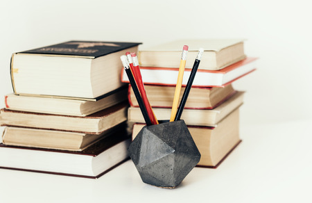 Stack of book education concept background, many books piles and pencils in concrete holder on white table with copy space for text Zdjęcie Seryjne - 122497152