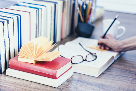 Stack of books education background, open book, female hand with pencil, glasses, and cup of tea with lemon