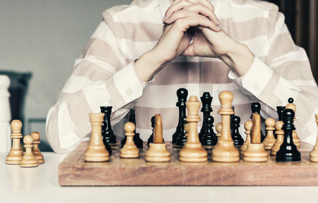 Wooden chess pieces on a chessboard, chess game woman player makes a move Stockfoto