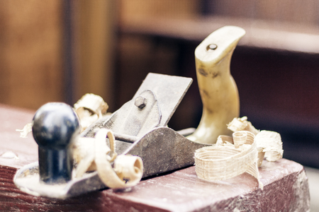 Joinery – old wooden plane and chips in a workshop of the carpenter, retro concept