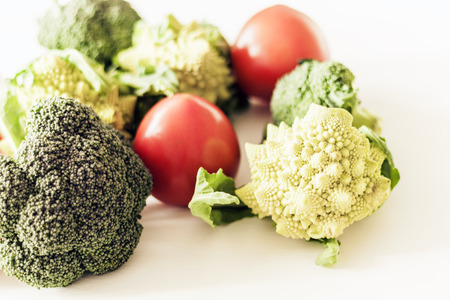 Ripe vegetables tomatoes romanesco broccoli on white wooden background with copy space for your text Banco de Imagens