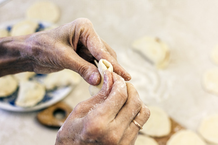 Dumplings. Dough with cabbage filling on the cook's hands