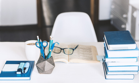 Modern stylish office work place with open book, glasses, office supplies and books, desk work concept in white and blue colors