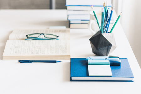 Modern stylish office work place with open book, glasses, office supplies and books, desk work concept in white and blue colors Stock fotó
