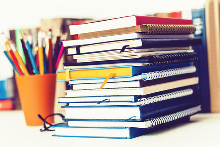 Notebooks piles, stack of books education back to school background, textbooks, glasses and pencils in plastic holder with copy space for text