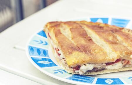 Fried calzone pizza with ham, mozzarella, tomatoes from bakery shop of Catania, Sicily, Italy