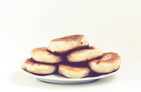 Traditional homemade fried patties or pies made of yeast dough in a rustic style on white plate