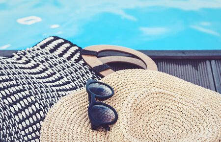 Vintage summer wicker straw beach bag, sun glasses, hat near swimming pool, tropical background 免版税图像