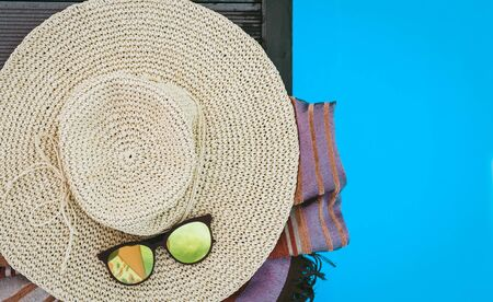 Vintage summer wicker straw beach hat, sun glasses, cover-up beachwear wrap near swimming pool, tropical background