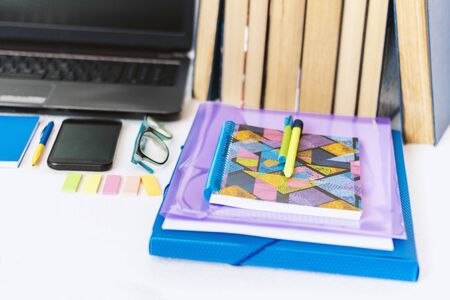 School stationery accessories - notebook, copybook, laptop, plastic folder, pens, glasses, paper clips, stickers, notepads, smartphone, stack of books education concept background
