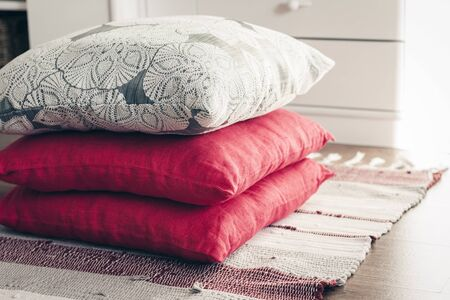 Cozy home interior decor, decorative pillows in front of white nightstand near a multi-colored rug background
