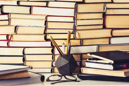 Stack of books, notebook, laptop, glasses in office background for education learning concept 写真素材