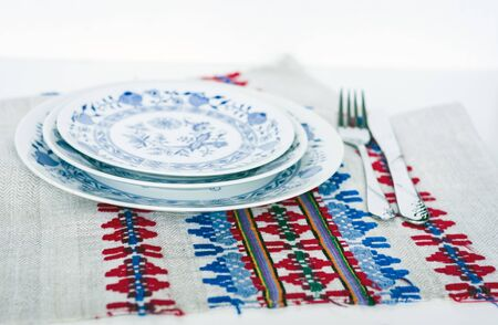 Table setting for dinner: white and blue plates, a fork, a knife on a woven cloth napkin with an embroidered pattern,  traditional handmade in Ukraine