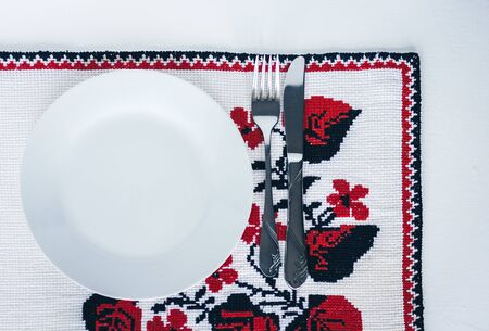 Table setting for dinner: a white plate, a fork, a knife on a woven cloth napkin with an embroidered pattern,  traditional handmade in Ukraine