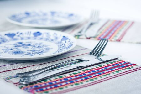 Table setting for dinner: white and blue plates, a fork, a knife on a woven cloth napkin with an embroidered pattern,  traditional handmade in Ukraine Archivio Fotografico - 128613222