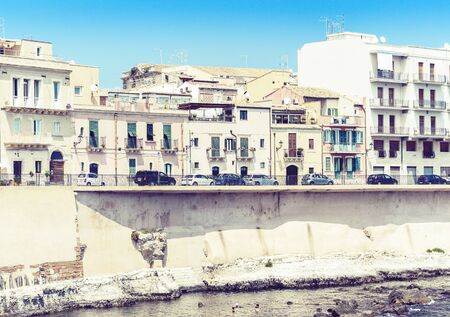View of old street, facades of ancient buildings in seafront of Ortygia (Ortigia) Island, Syracuse (Siracusa), Sicily, Italy Stock Photo