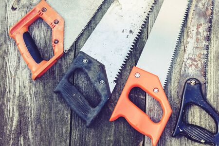 hand saws well used on wooden boards background, retro concept. Stock Photo