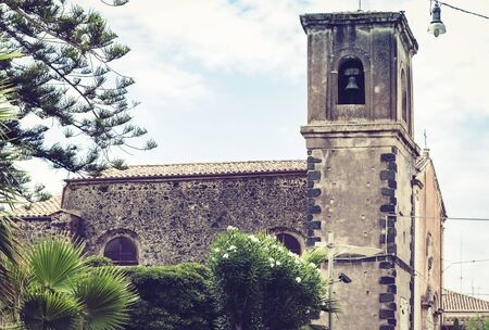 Travel to Italy -  historical square of Acitrezza, Catania, Sicily, facade of old tower building