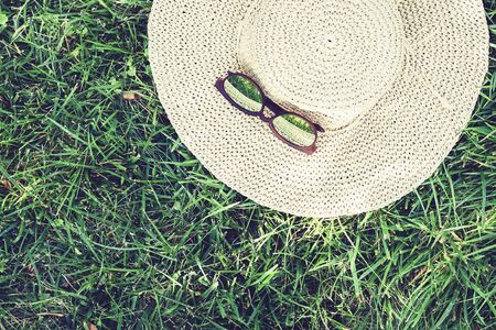 female wicker hat and sunglasses on the lawn on the grass in the park Stockfoto - 128614420