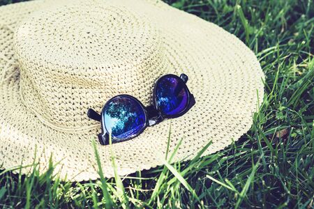 female wicker hat and sunglasses on the lawn on the grass in the park